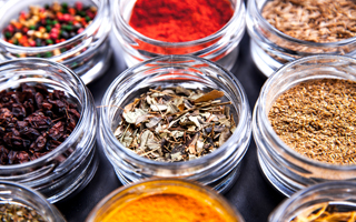 Spices on black background in special jars