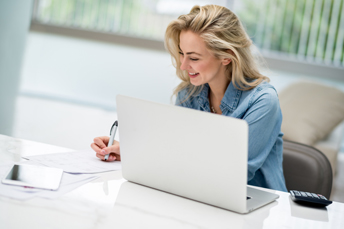 woman writing in front of computer